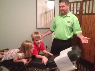Doctor Brown speaking to two children who are laying on an adjustment table